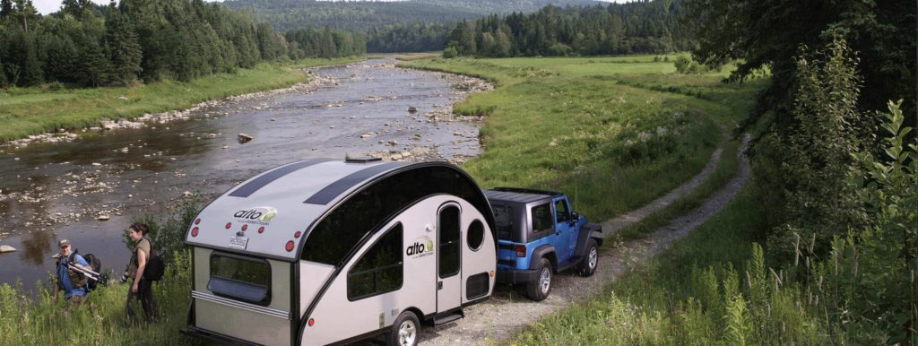 F-SEries Alto travel trailer being towed by a jeep in the mountains
