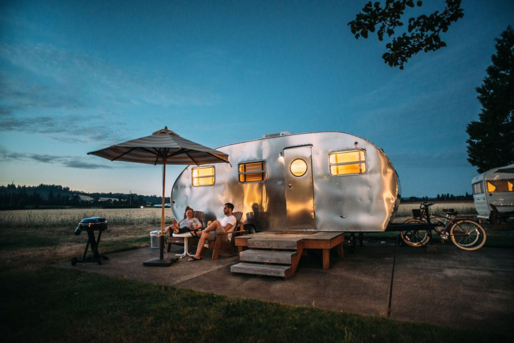 RV setup at fancy campground with bikes, chairs, table, umbrella, and great view