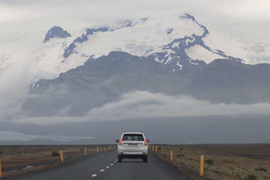 A car on a highway in Iceland with a large mountain in the background