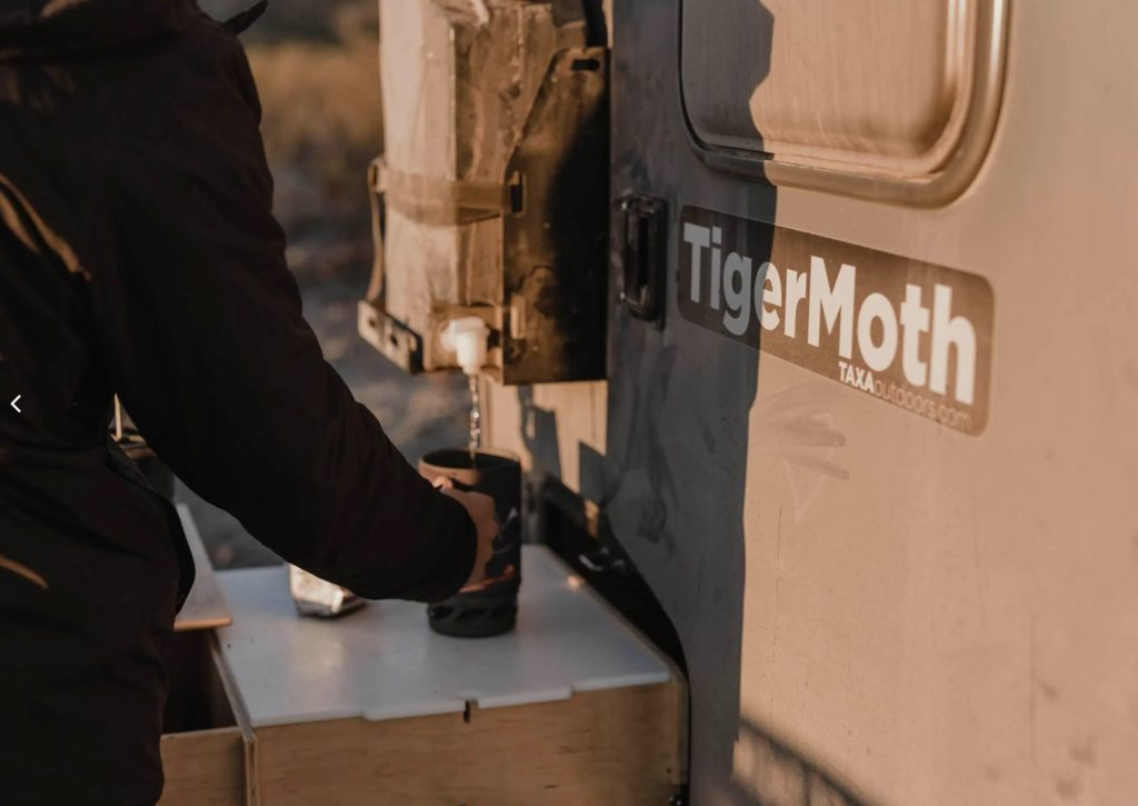 Image of pouring coffee from Nato tank on back of Tiger Moth trailer