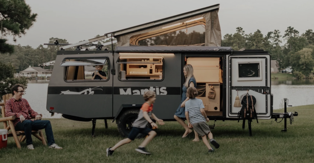 Children playing in front of Mantis camping trailer