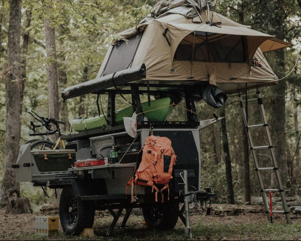 Taxa outdoors Woolly Bear travel trailer exterior shot in the woods