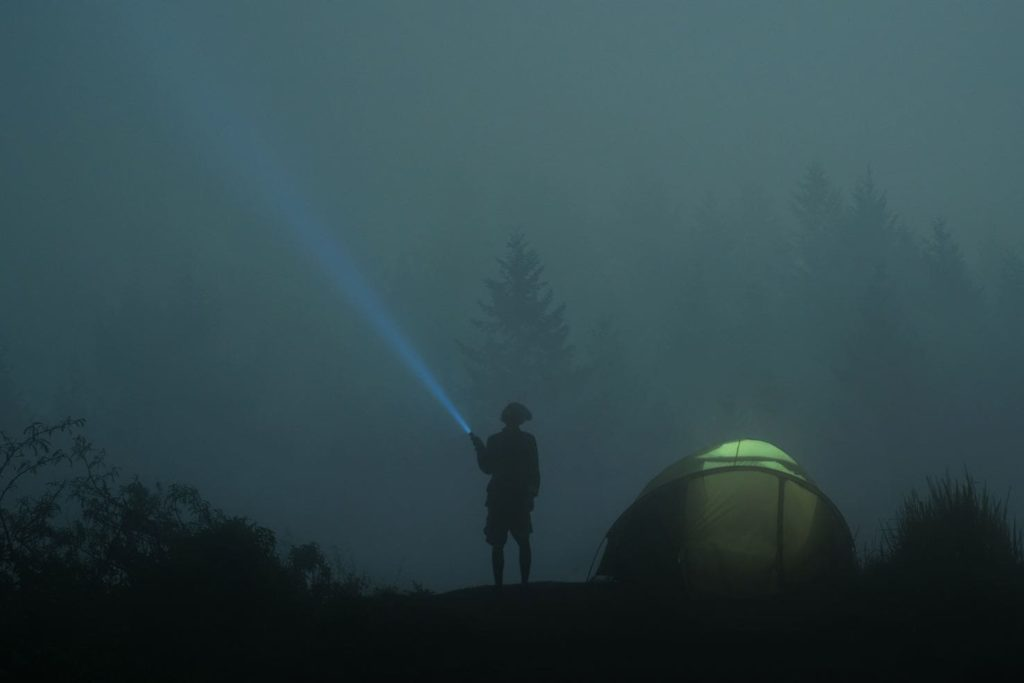 Camping in fog with flashlight and tent hidden