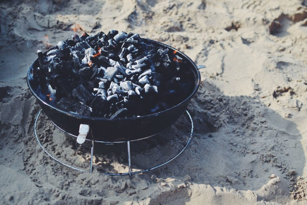 Campfire over sand with still hot smoldering coals