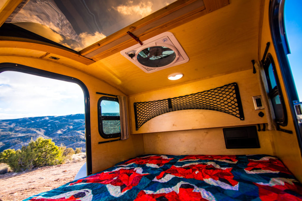 bedding in cabin of trailer with view outside