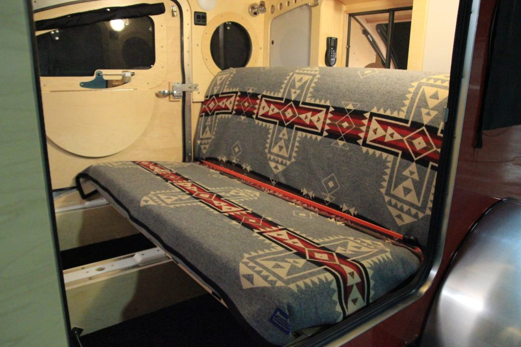Close up of bed turned couch in teardrop trailer