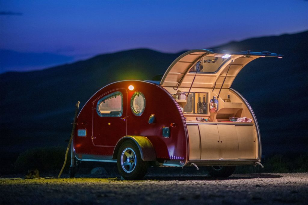 red Vistabule camper at night with galley open