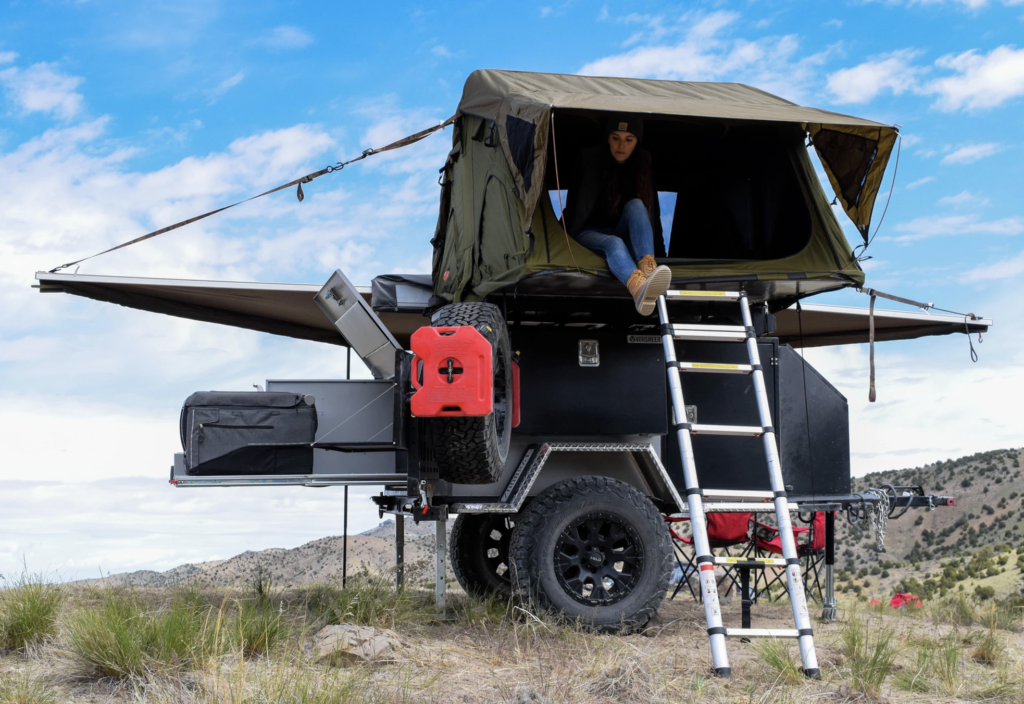 Woman sitting in roof tent on XER trailer